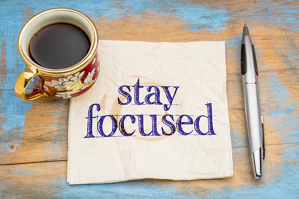 stay focused reminder or advice - handwriting  on napkin with cup of coffee against a grunge painted wood