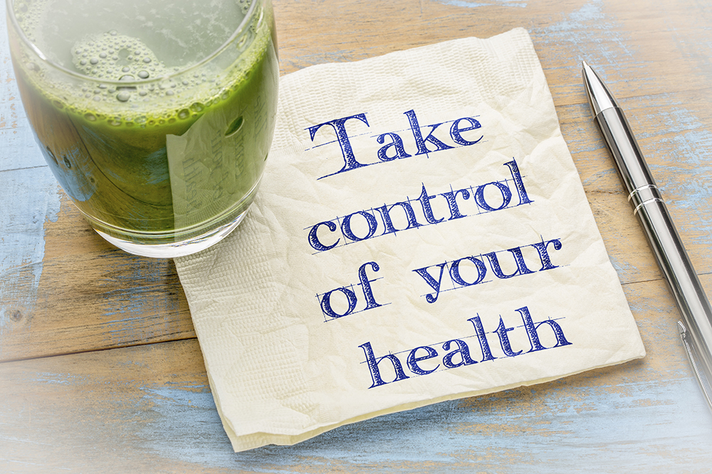 Take control of your health advice - handwriting on a napkin with a glass of fresh, green, vegetable juice